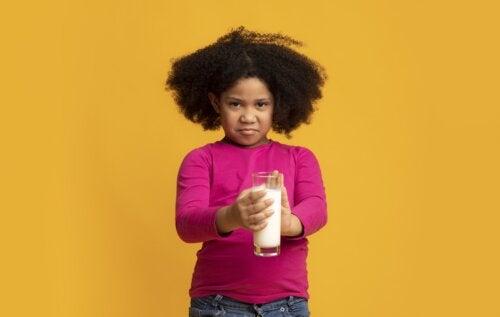 Niña rechazando un vaso de leche debido a que sufre intolerancia transitoria a la lactosa.