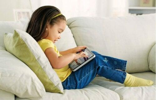 Niña jugando con la tablet para aprender ortografía.