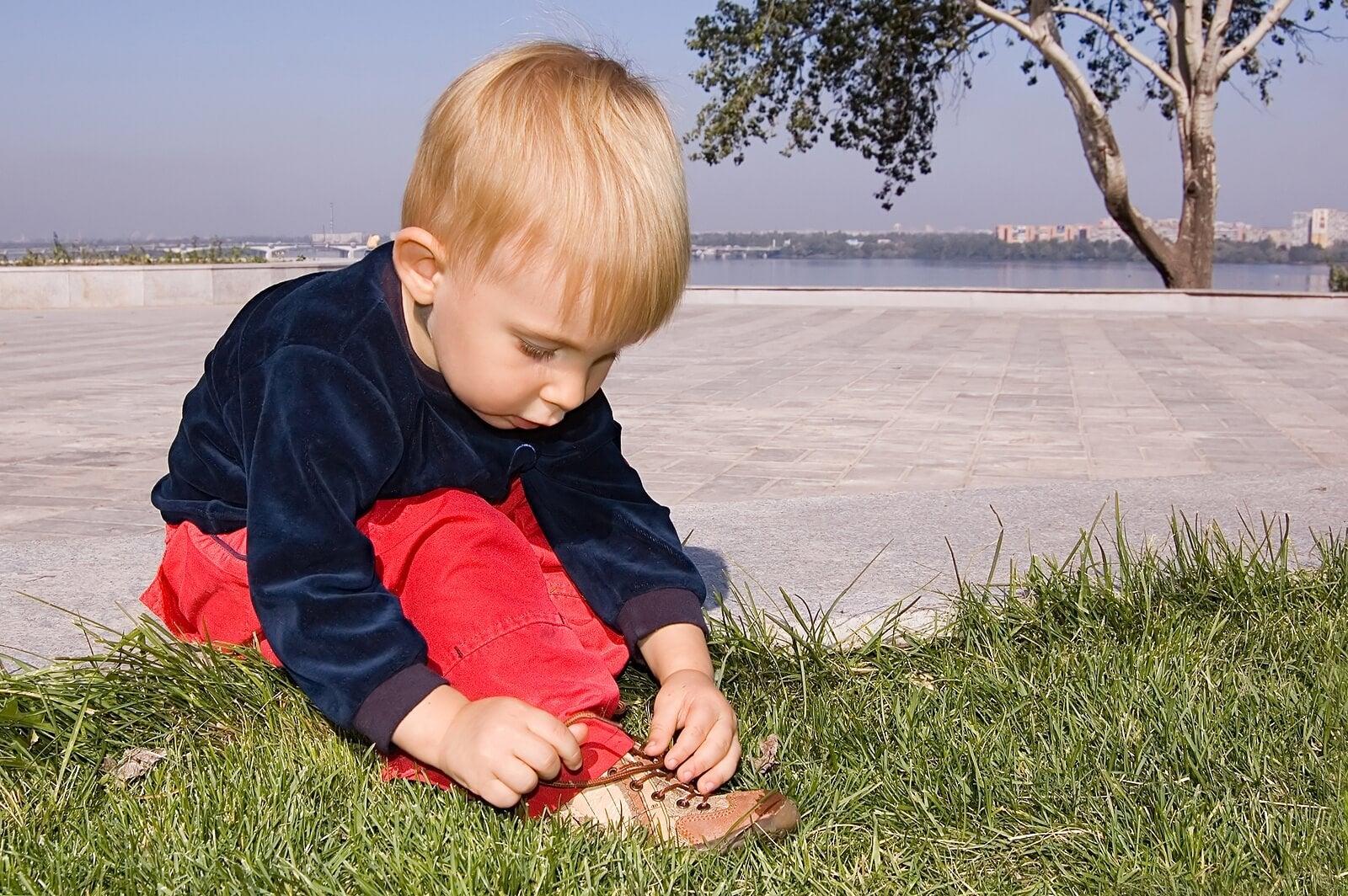 Niño aprendiendo a atarse los cordones de los zapatos.