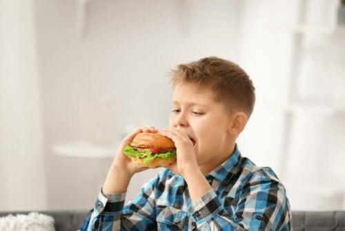 Niño comiéndose una hamburguesa.