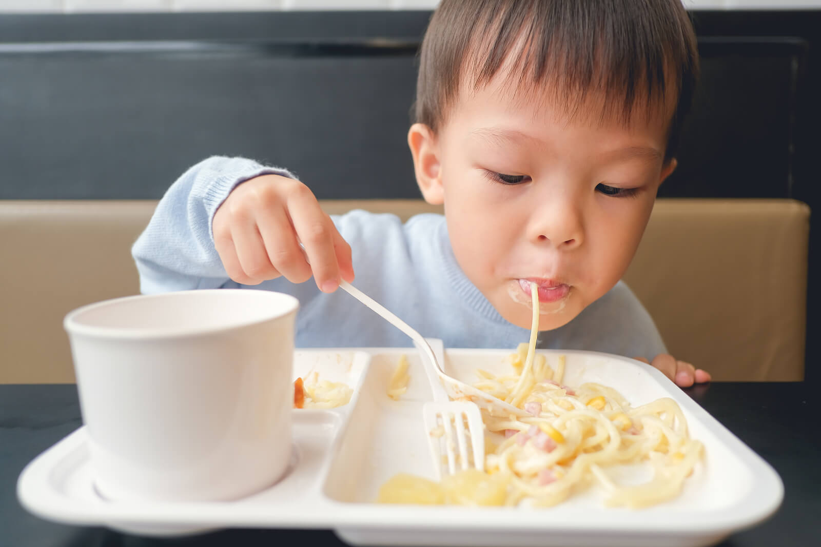 Niño comiendo pasta carbonara incluida en su menú infantil.
