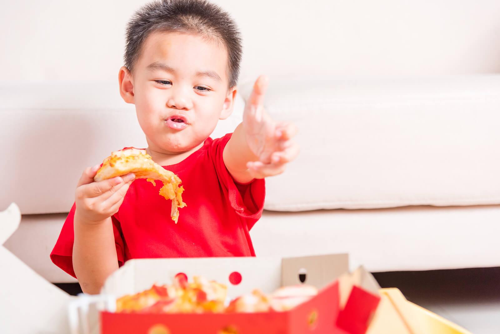 Niño comiendo pizza de un menú infantil, uno de los factores implicados en la regulación del apetito en niños.