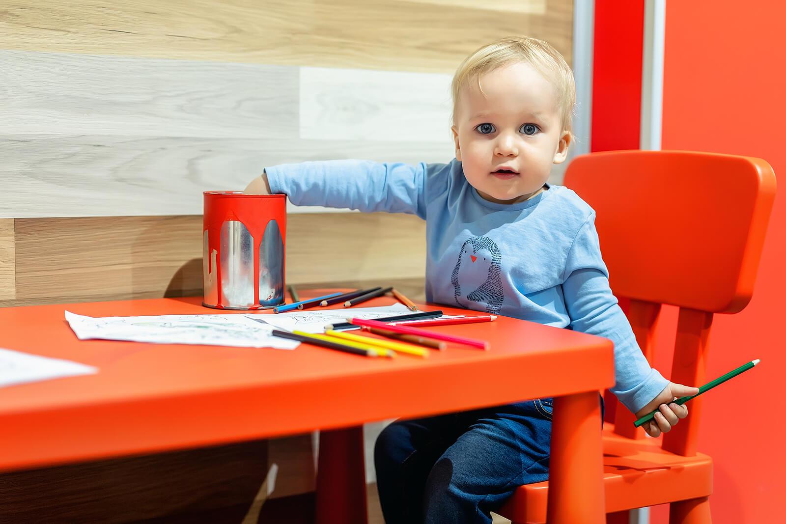 Niño dibujando con muchos colores, pues el dibujo es la primera escritura de los pequeños.