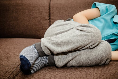 Niño con dolor abdominal tumbado en el sofá.