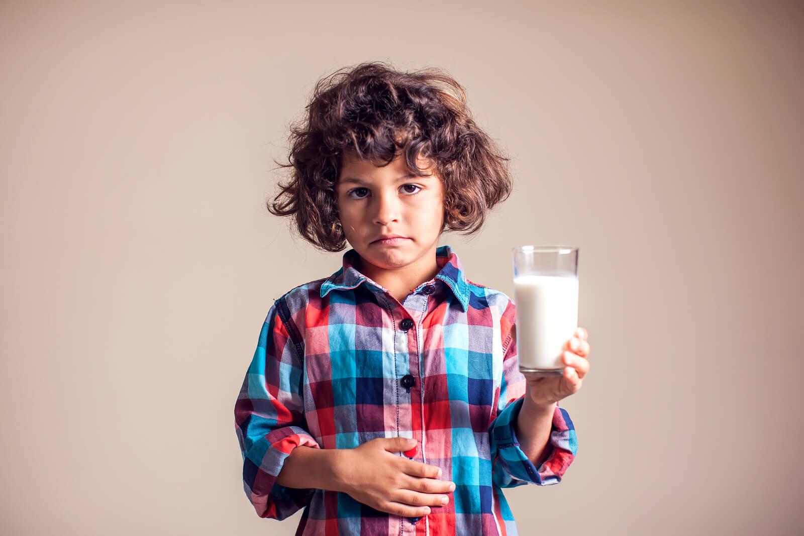 Criança com dor de barriga e um copo de leite na mão devido a intolerância transitória à lactose.