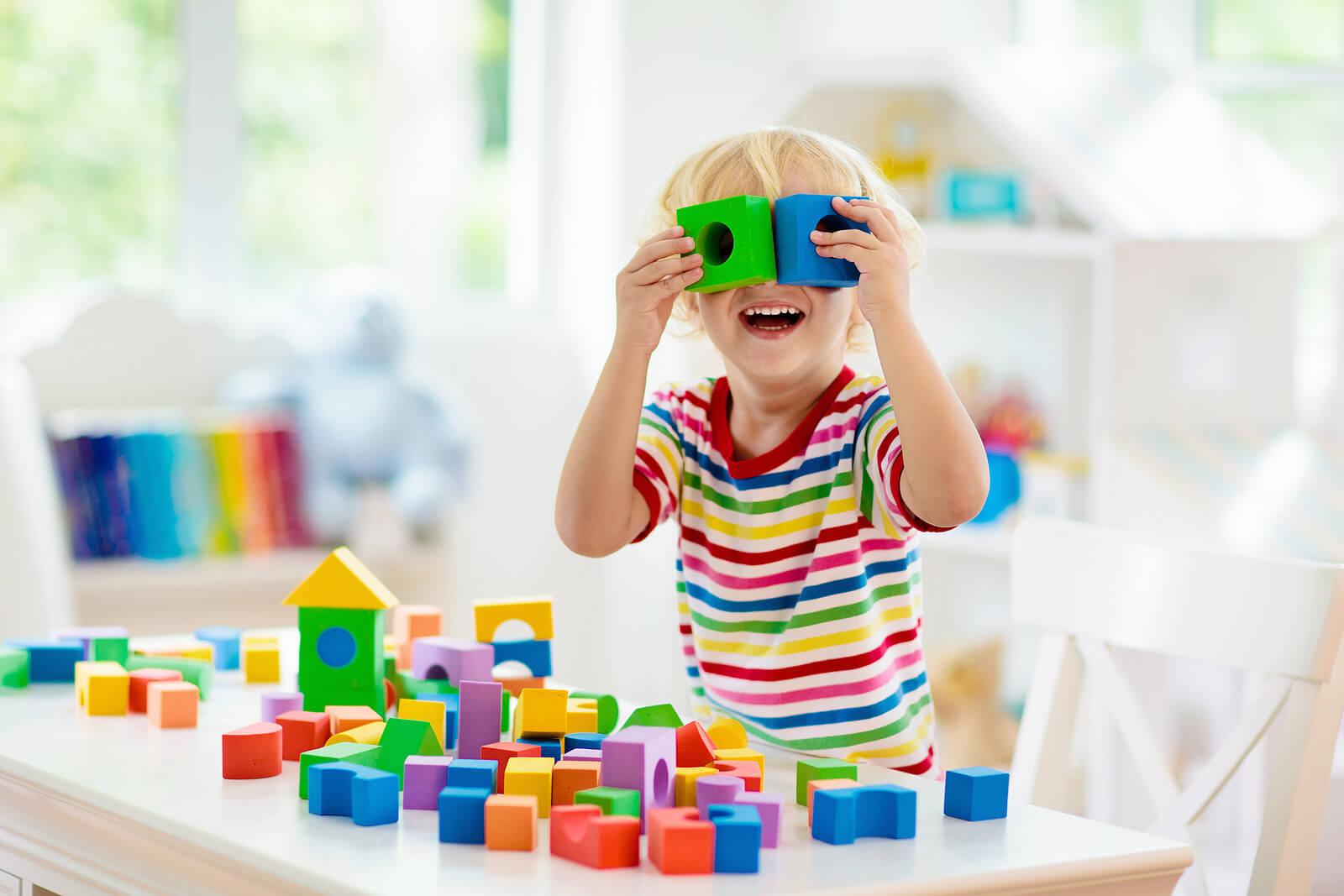 Niño jugando con unas piezas de madera para desarrollar el razonamiento deductivo.