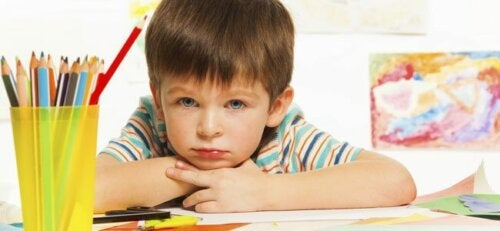 Niño pensativo mientras dibuja y pinta.