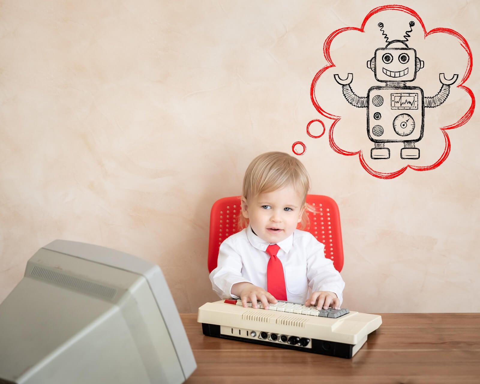 Niño con un ordenador pensando en un robot.