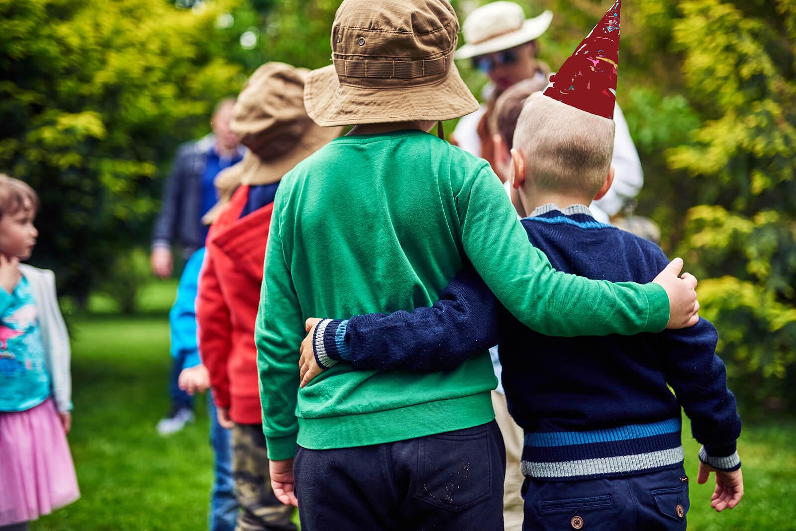 Niños dándose un abrazo durante una excursión por el campo como parte de su desarrollo social.