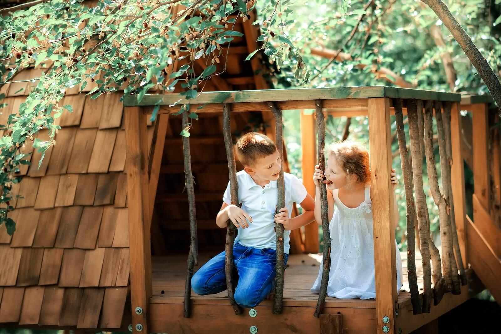 Niño jugando al escondite en la cabaña del bosque tras rifar antes de jugar.