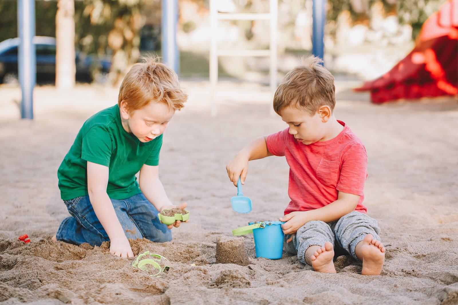 Niño jugando a hacer castillos de arena para fomentar su desarrollo motor grueso.