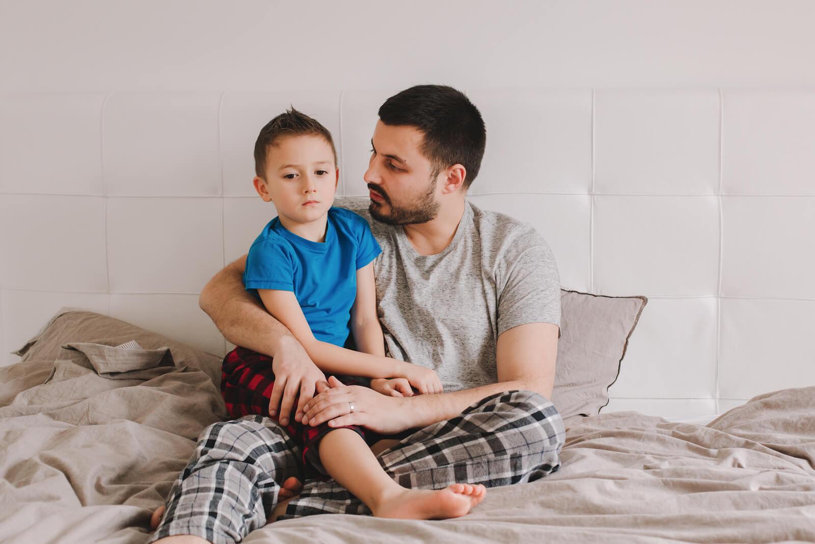 Padre hablando con su hijo sentados en la cama para mejorar la disfluencia del habla del pequeño.