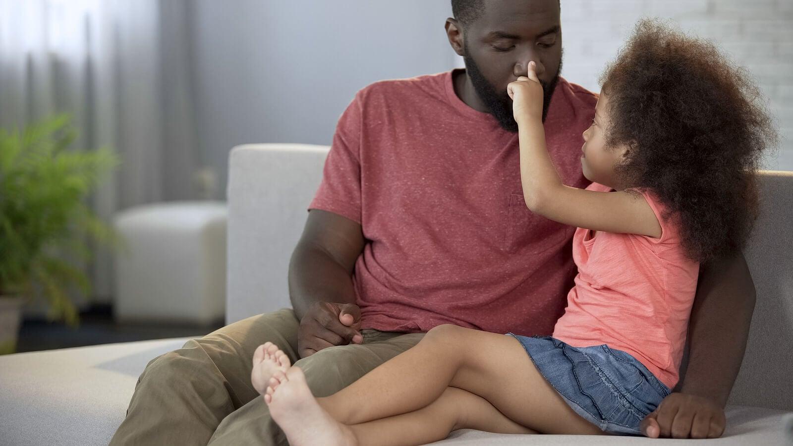 Padre jugando con su hija con mucho afecto.