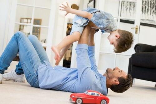 Padre jugando con su hijo en el salón de casa.