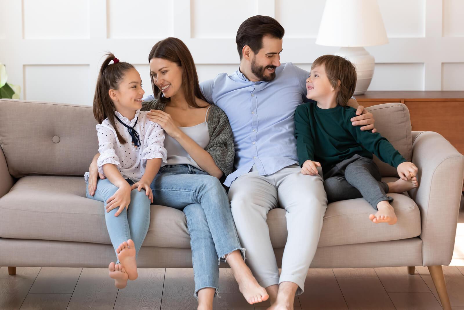 Padres llenado de afecto a sus hijos en el sofá de casa.