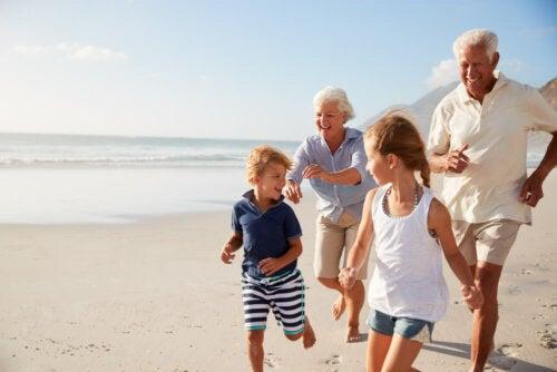 Abuelos y nietos corriendo por la playa.