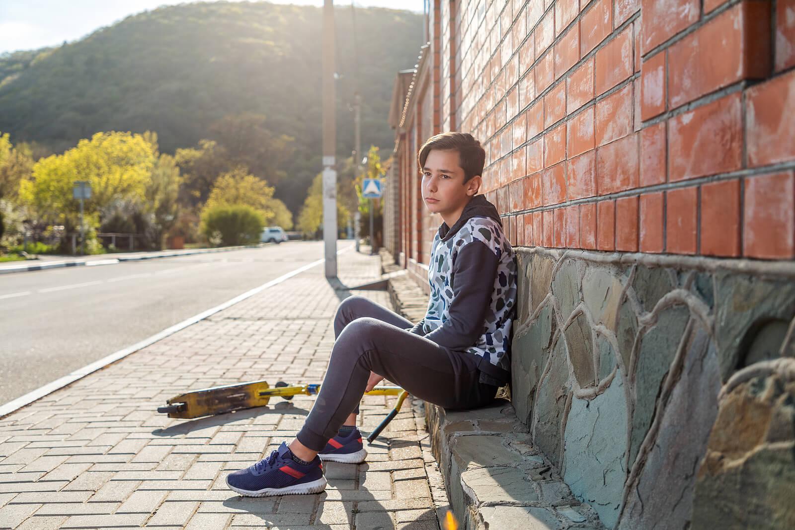 Chico adolescente con su patinete solo sufriendo el síndrome de la adolescencia normal.