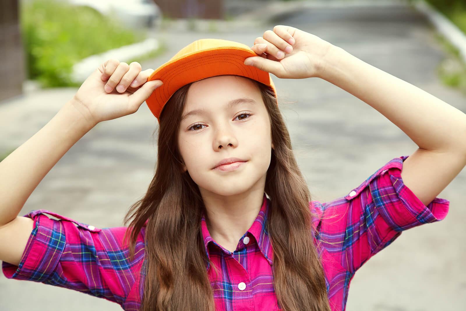 Chica adolescente con una gorra posando.