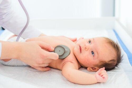 Pediatra escuchando el corazón de un bebé para comprobar que no tenga un soplo.