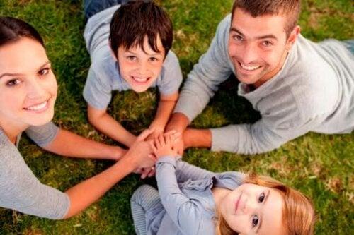 Familia tumbada en el césped con las manos unidas.