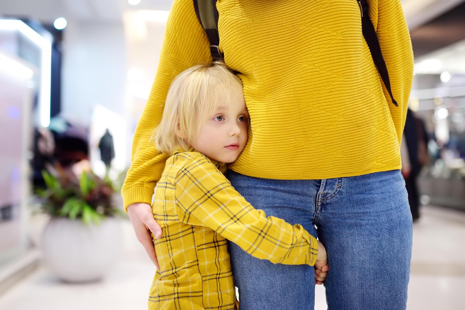 Niño abrazado a la pierna de su madre.