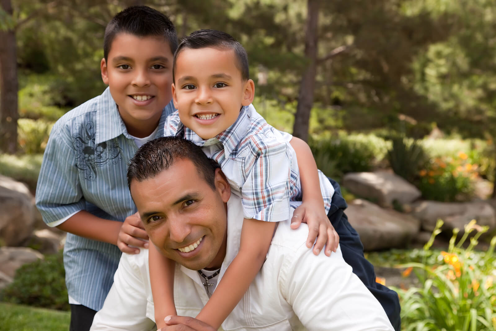 Hijos abrazando a su padre en medio de la naturaleza debido a la importancia del contacto físico en la educación de los hijos.