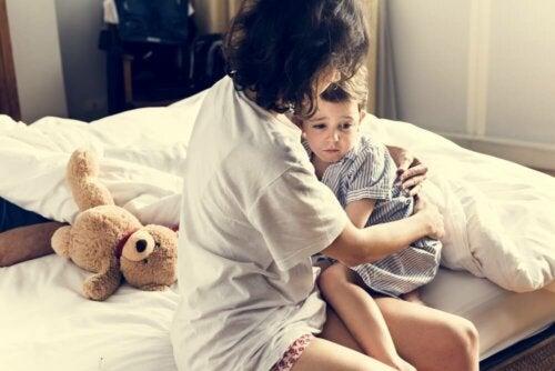 Madre abrazando a su hijo en la cama después de tener una pesadilla.