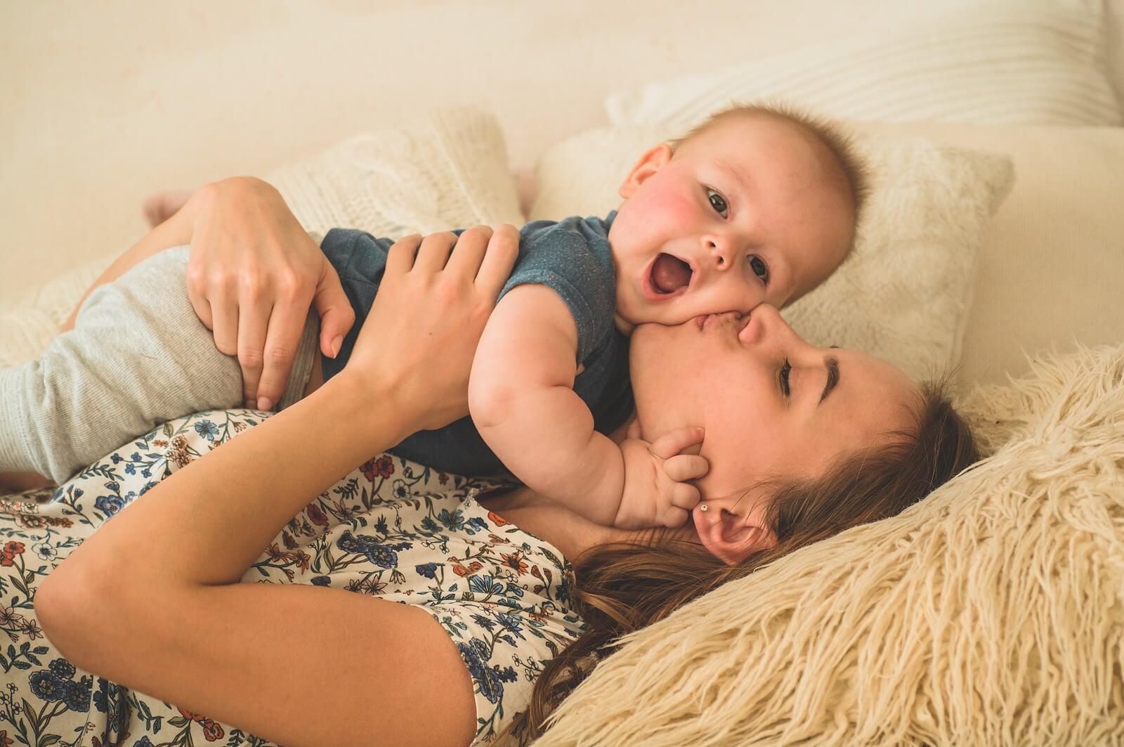 Mamá besando y abrazando a su bebé porque los recuerdos de los niños se componen de emociones.