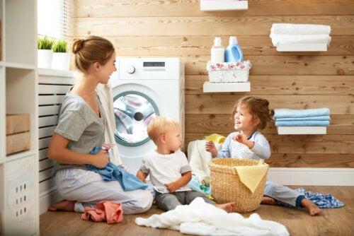 Mamá enseñando a sus hijos a poner una lavadora.