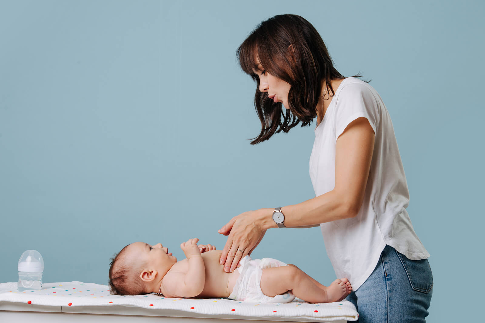 Madre en el cambiador con su bebé hablando mediante el baby sign.