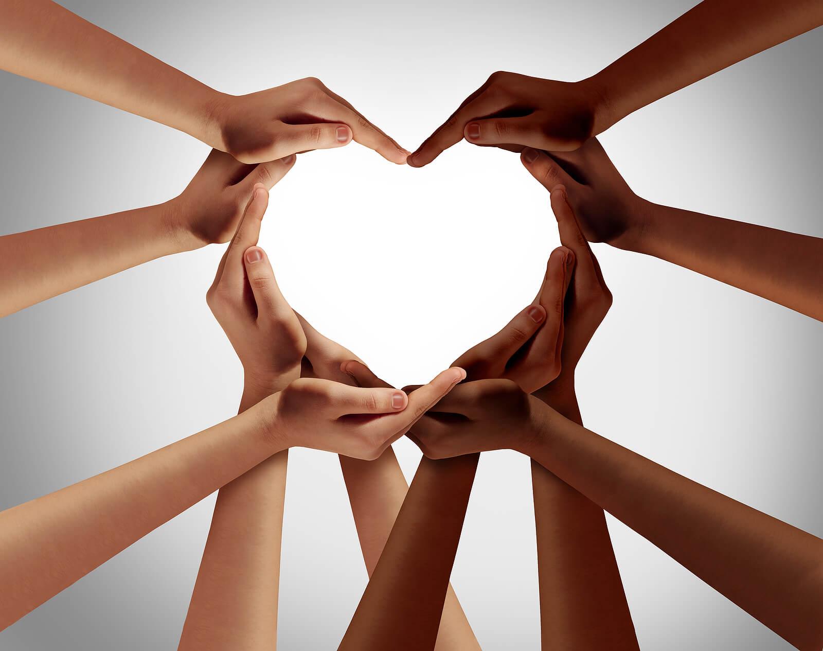 Manos de diversos colores y razas formando un corazón.