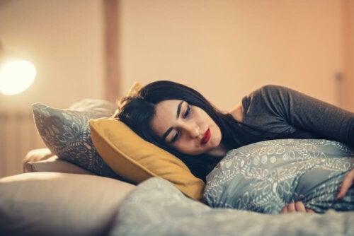Mujer triste tumbada en el sofá abrazando cojines.