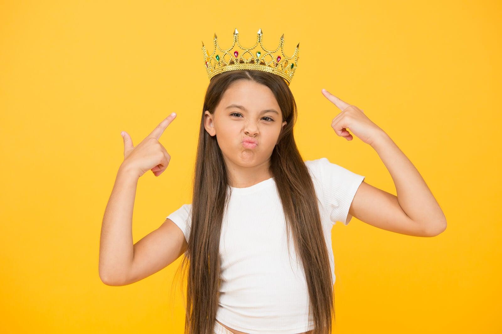 Niña con una corona en la cabeza mostrando su egocentrismo.