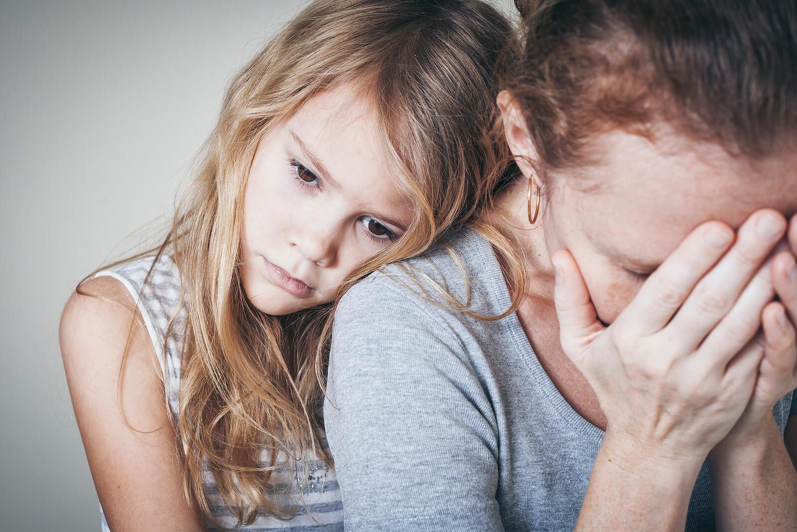 Hija apoya en el hombro de su madre para darle apoyo mientras sufre un ataque de ansiedad.