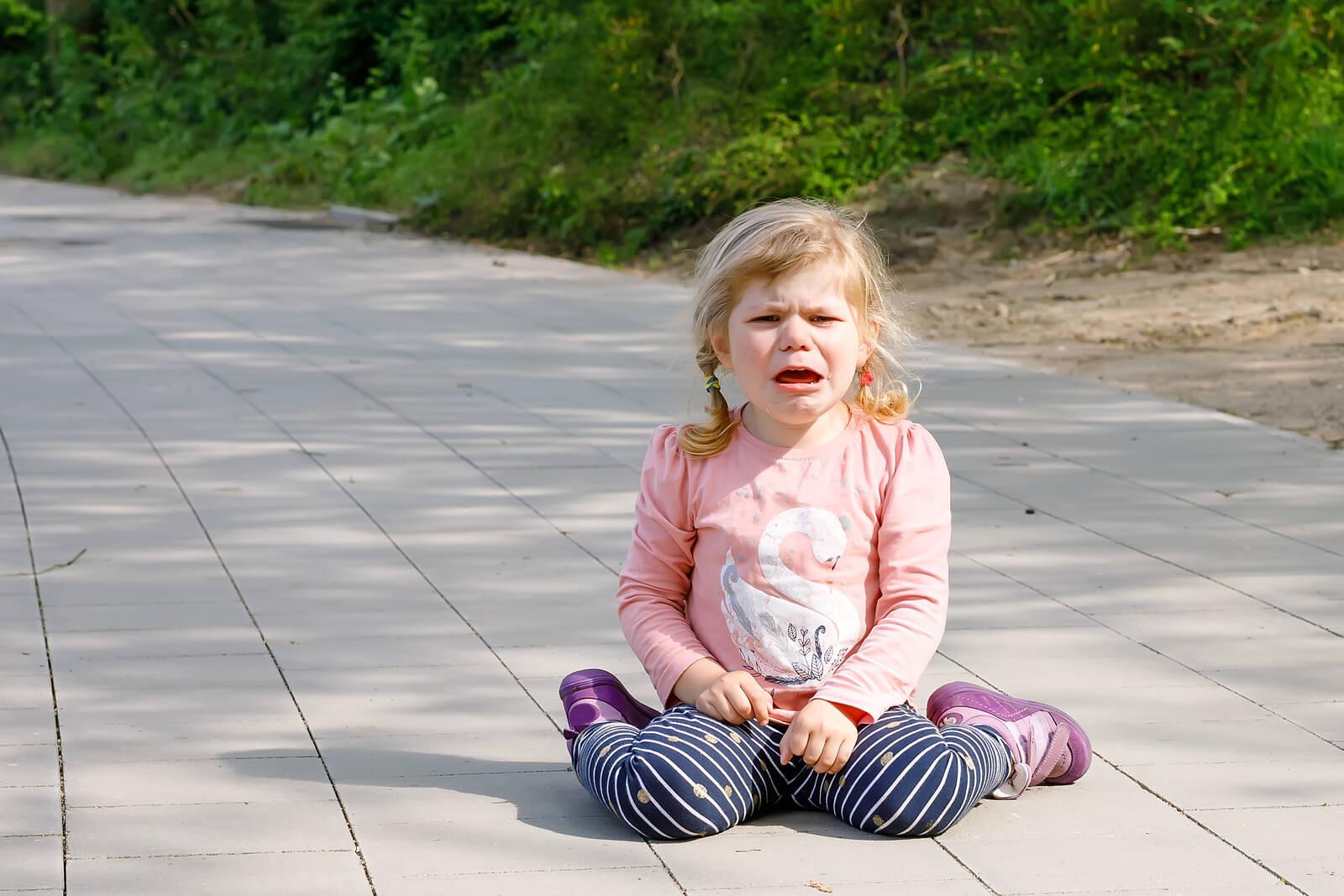 Niña en el suelo llorando.
