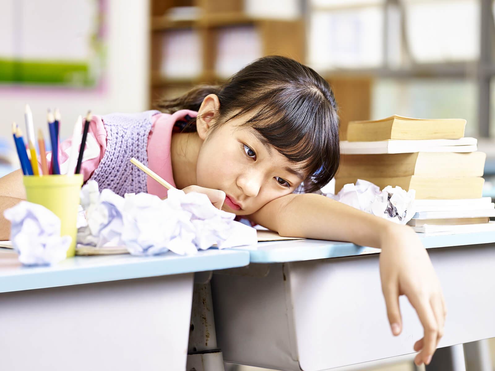 Niña sentada en el pupitre de la escuela sin motivación por aprender.