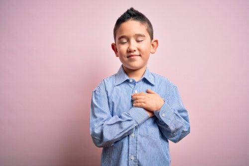 Niño agradecido con las manos en el pecho.