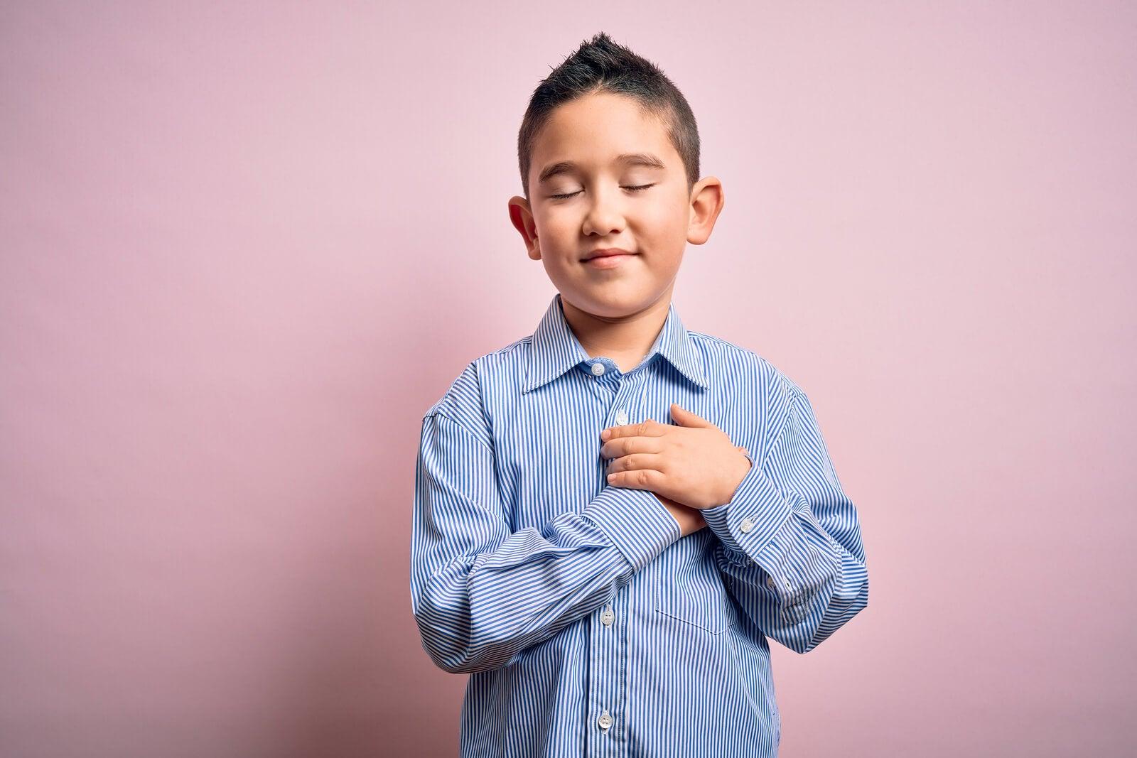 Niño agradecido con las manos en el pecho porque sabe qué tan importante es la paz.