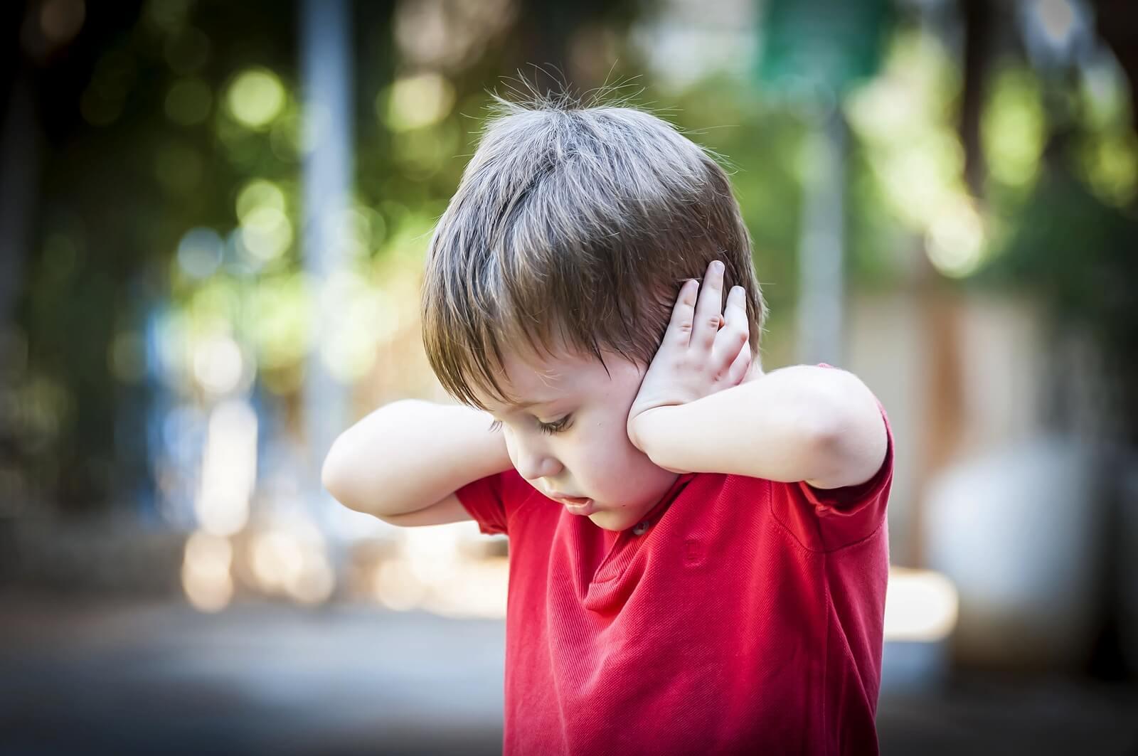 Niño asustado tapándose las orejas.