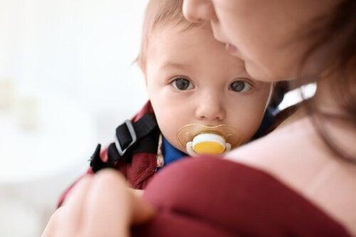 Niño en brazos de su madre con el chupete en la boca.
