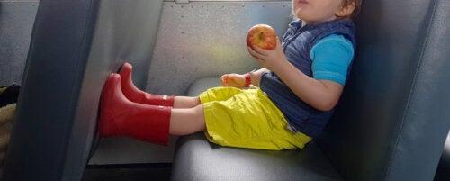 Niño comiéndose una manzana en el autobús con unas botas de agua.