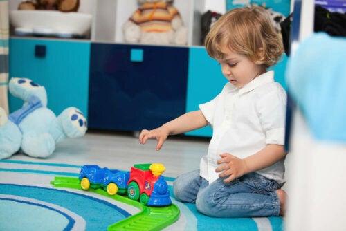 Niño de dos años jugando con un tres sentado en el suelo.