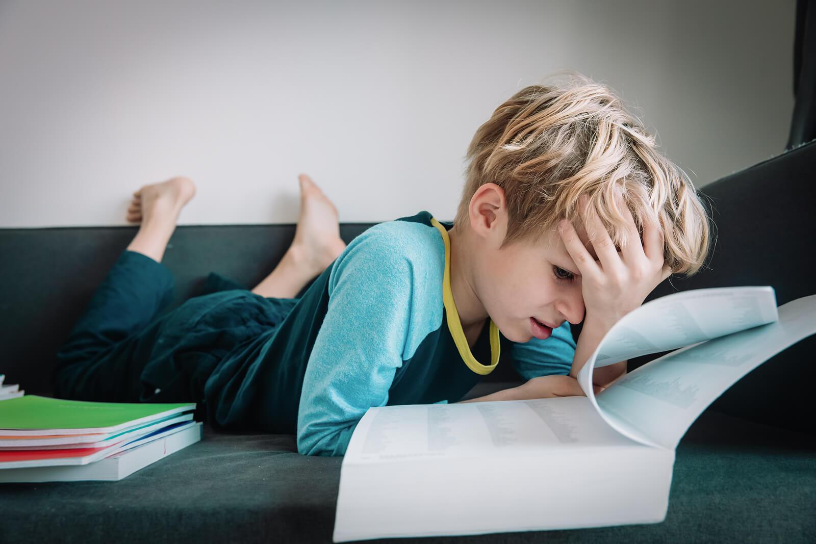 Niño en el sofá de casa con los libros alrededor porque tiene miedo a los exámenes.
