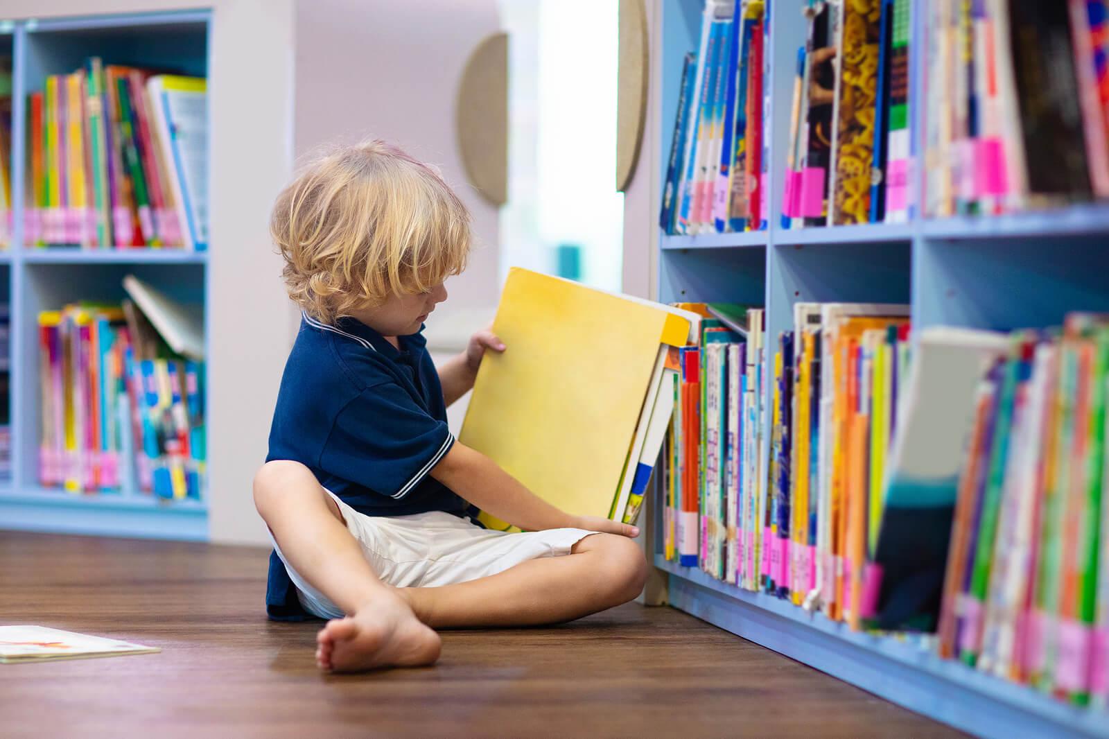 Niño cogiendo un libro y leyendo en la biblioteca de aula.