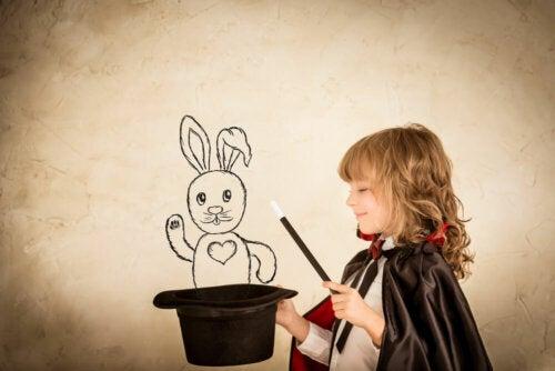 Niño sacando un conejo de una chistera mediante la magia.