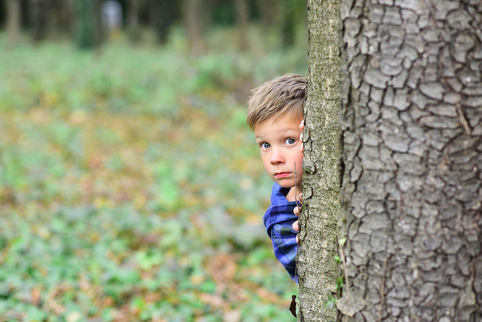 Niño escondido detrás de un árbol debido a sus miedos evolutivos.