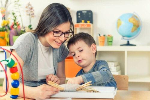 Niño con necesidades de compensación educativa siendo ayudado por su profesora.