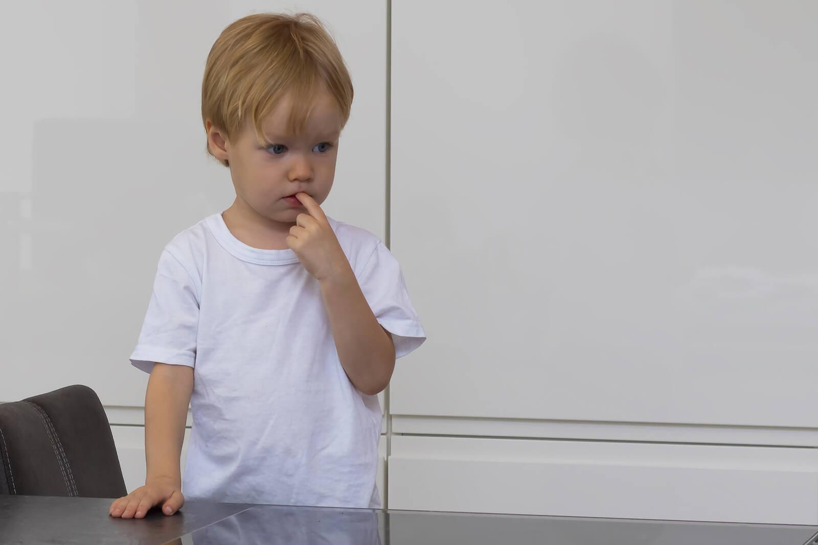 Niño con el dedo en la boca pensando en cómo poner a prueba los límites de sus padres.