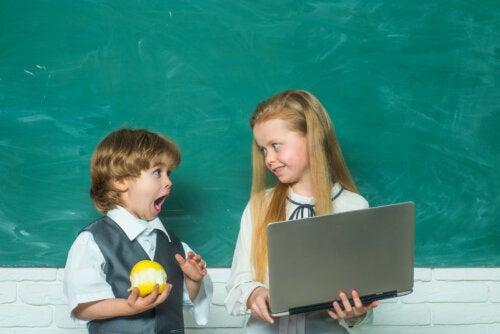Niño con una manzana junto a su compañera de clase, que tiene un ordenador en las manos.
