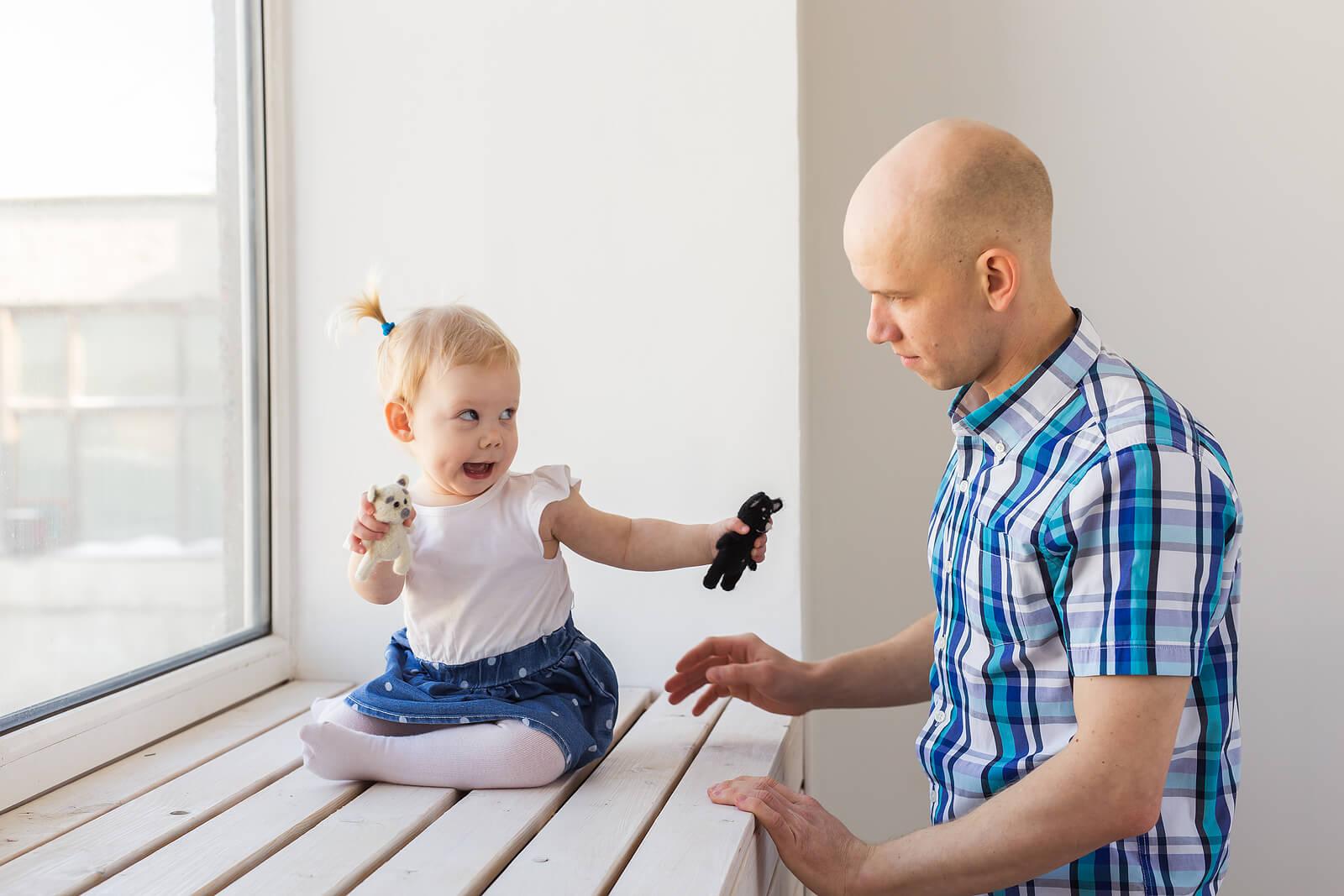 Papá con su hija hablando mediante el baby signing.